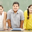 Three happy children standing at board, posing beside the table — Stock Photo