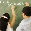 Back to school - boy and girl writing on board in classroom — Stok fotoğraf