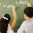 First love - boy and girl writing on board in classroom — Foto de Stock