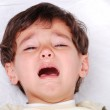 Little cute kid is crying on white sheet — Stock Photo #8844072