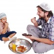 Stock Photo: Young muslim mand his son with prepared food for iftar in Ramadan