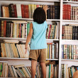 Kid trying to reach a book in the library — Stock Photo #8844310