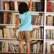 Kid trying to reach a book in the library — Stock Photo #8844317