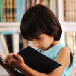 Kid with book in library — Stock Photo