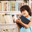 Kid with book in library — Foto Stock