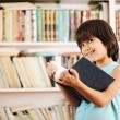 Kid with book in library — Stock Photo #8844329