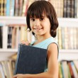 Kid with book in library — Stock Photo #8844331