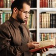 Young man reading book in library — Stock Photo