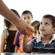 Stock Photo: Hungry children in refugee camp, distribution of humanitarifood
