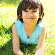Young child laying on the grass - Stock Photo