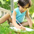 Young boy outdoors on the grass writing — Stok fotoğraf