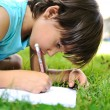 Young boy outdoors on the grass writing — Stock Photo