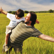 Man in wheat field with boy — Stock Photo