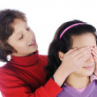 Girl covering a girls eyes to see if she can guess who is behind her — Stock Photo #8844587