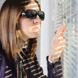 Young brunette woman in the sunlight looking through jalousie on window — Stock Photo