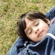 Happy dreaming child on green meadow — Stock Photo