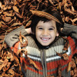 A little child playing in the autumn leaves — Stock Photo