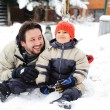 Happy father and cute son together on snow in front of house - Stock Photo