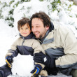 Stock Photo: Happy father and cute son playing together on snow