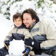 Happy father and cute son playing together on snow — Stock Photo