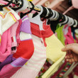 Close-up of a female  customer looking for children clothes in a fashion st - Stock Photo
