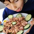 Kid eating fish - Stock Photo