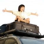 niño viajando en las bolsas, la parte superior del coche — Foto de Stock