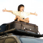 kleiner Junge Reisen auf Taschen, oben auf dem Wagen — Stockfoto