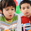 Two little boys blowing candles on cake, happy birthday party - Stock Photo