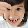 Lost milk-tooth, cute boy with long hair holding his tooth on thread — Stock Photo #8845795