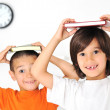 Happy cute boys at home, lovely little brothers with books on heads — Stock Photo #8845825