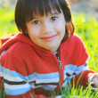 Little cute boy laying on morning summer grass with natural beautiful light — Stockfoto