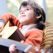 Royalty-Free Stock Photo: Portrait of young boy playing acoustic guitar at home