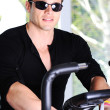 Stock Photo: Handsome man doing spinning at the gym