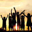 Silhouette, group of happy children playing on meadow, sunset, summertime — Stock Photo #8846429