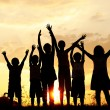 Стоковое фото: Silhouette, group of happy children playing on meadow, sunset, summertime