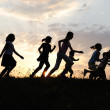 Silhouette, group of happy children playing on meadow, sunset, summertime — Stock Photo #8846471