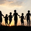 Silhouette, group of happy children playing on meadow, sunset, summertime — Stock Photo #8846622