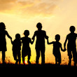 Silhouette, group of happy children playing on meadow, sunset, summertime — Stock Photo #8846625