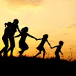 Silhouette, group of happy children playing on meadow, sunset, summertime — Stock Photo #8846650