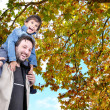 Happy father and his son on the back, fall — Stock Photo