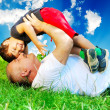 Stock Photo: A parent and little boy laying on grass