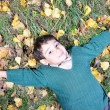 Little cute kid laying on the fall ground — Stockfoto