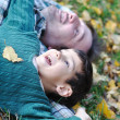 Happy positive young man with his kid on fall ground — Stock Photo #8847678