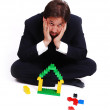 Young mane wearing suit is making a house with cubes toys — Stock Photo