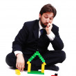 Young mane wearing suit is making a house with cubes toys — Stock Photo #8848065