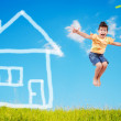Cute girl is jumping on green meadow with abstract house on — Stock Photo