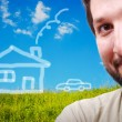 Happy young man with imagination of house and car on beautiful meadow — Stock Photo