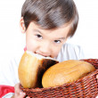 A little cute kid holding bread and biting it — Stock Photo