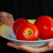 Red tomato in female hands with black background — Stockfoto